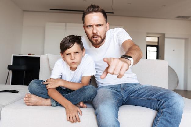 Porträt des ernsthaften konzentrierten vaters und des sohnes, die finger auf sie zeigen, während sie auf sofa in der wohnung sitzen