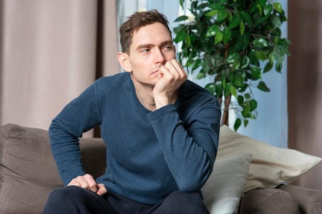 Porträt des ernsthaften traurigen verärgerten kerls, des jungen einsamen gutaussehenden nachdenklichen müden gelangweilten mannes, der am sofa sitzt