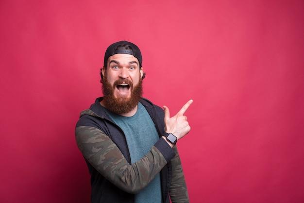 Porträt des erstaunten bärtigen hipster-mannes, der weg auf copyspace zeigt