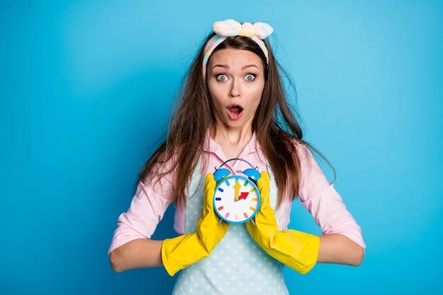 Porträt des erstaunten dienstmädchens, das den countdown der handuhr hält