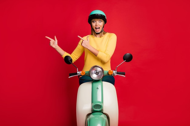 Porträt des erstaunten fröhlichen mädchens, das auf moped sitzt und direkten finger leeren raum zeigt