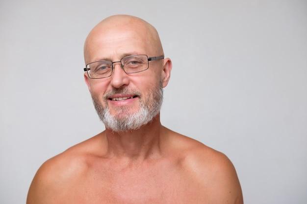 Porträt des erwachsenen bärtigen mutigen skinhead ergrauten mannes in den brillen