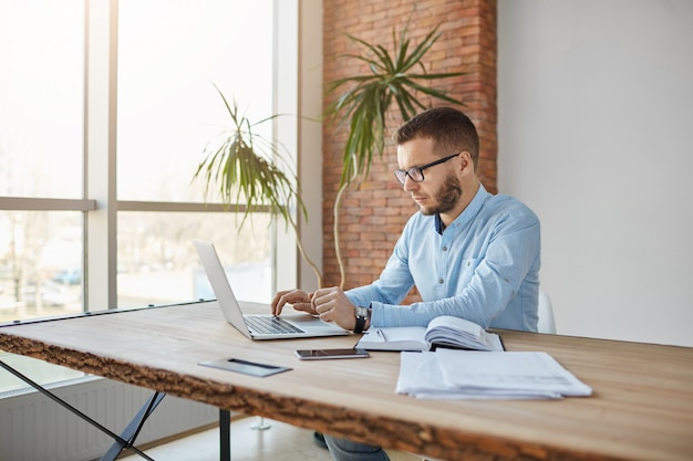 Porträt des erwachsenen ernsthaften männlichen firmendirektors, der im bequemen büro sitzt und firmengewinne auf laptop überprüft