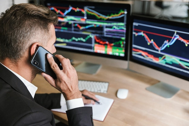 Porträt des erwachsenen geschäftsmannes 30s, der anzug trägt, der auf handy spricht, während mit digitaler grafik auf computer im büro arbeitet