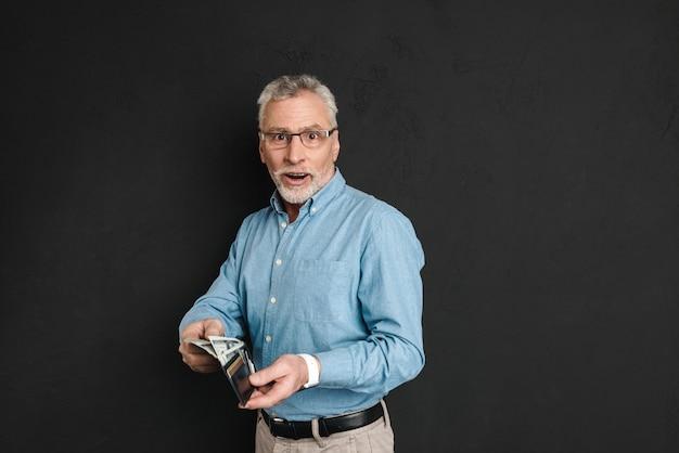 Porträt des erwachsenen mannes 60s mit grauem haar und bart, der brieftasche mit geld aufwirft und hält, lokalisiert über schwarzer wand