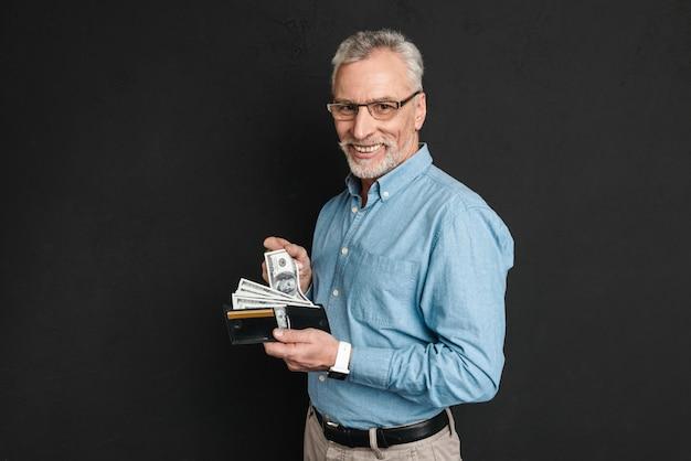 Porträt des erwachsenen mannes 60s mit grauem haar und bart lächelnd und hält brieftasche voll von dollarnoten, lokalisiert über schwarzer wand