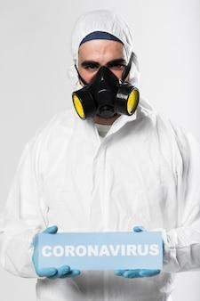Porträt des erwachsenen mannes coronaviruszeichen halten