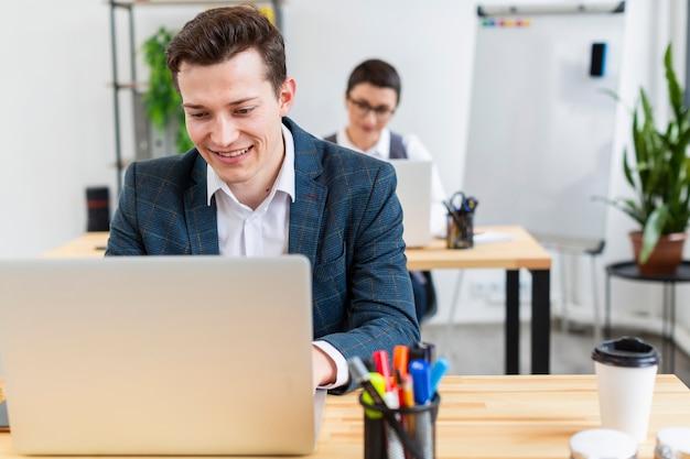 Porträt des erwachsenen mannes, der am laptop arbeitet