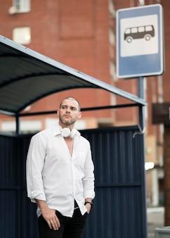 Porträt des erwachsenen mannes, der auf den bus wartet