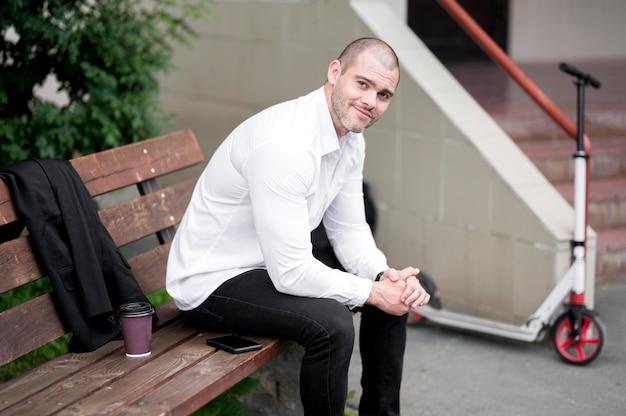 Porträt des erwachsenen mannes, der auf einer bank sitzt