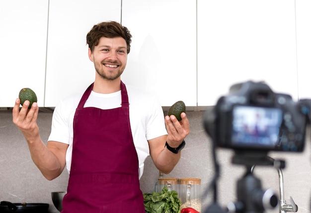 Porträt des erwachsenen mannes, der avocados vor der kamera hält