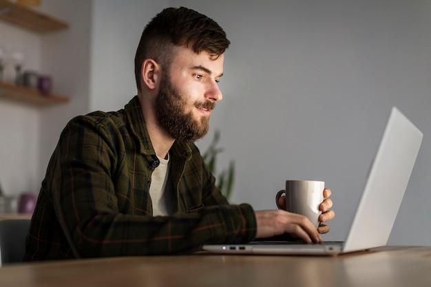 Porträt des erwachsenen mannes, der entfernte arbeit genießt