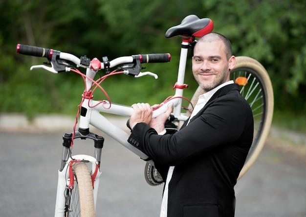 Porträt des erwachsenen mannes, der fahrrad trägt