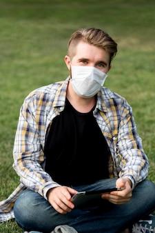 Porträt des erwachsenen mannes, der mit gesichtsmaske aufwirft