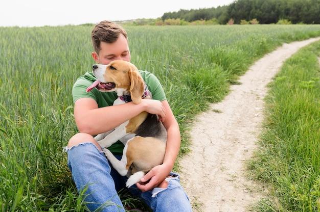 Porträt des erwachsenen mannes, der natur mit hund genießt