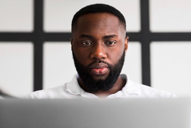 Porträt des erwachsenen mannes, der seinen laptop durchsucht