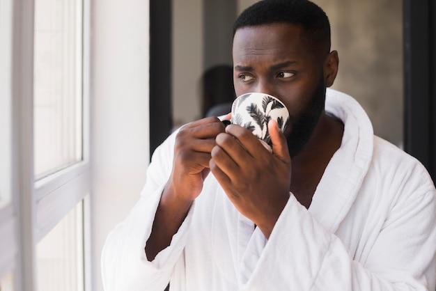 Porträt des erwachsenen mannes, der tasse kaffee genießt