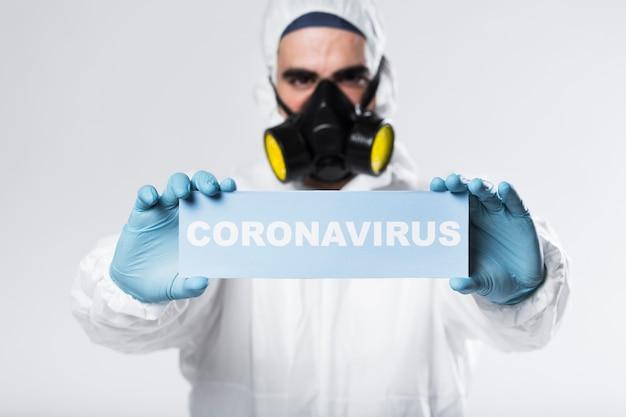 Porträt des erwachsenen mit der gesichtsmaske, die coronaviruszeichen hält