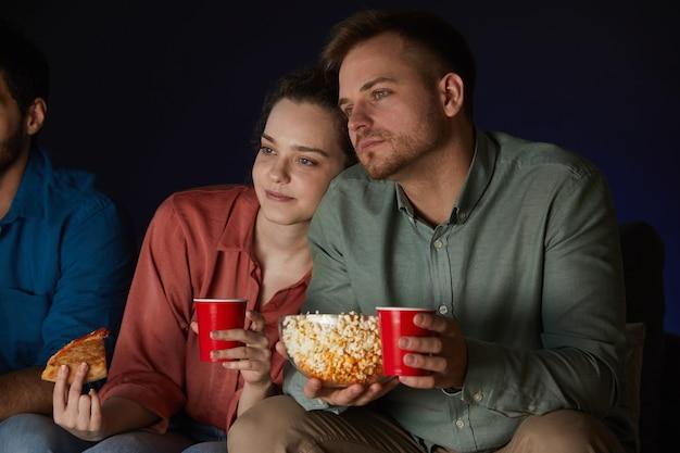 Porträt des erwachsenen paares, das filme zu hause beim essen von snacks und popcorn sieht, die auf sofa im dunklen raum sitzen