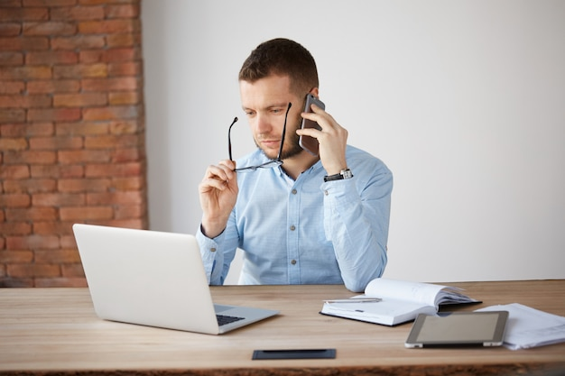 Porträt des erwachsenen unrasierten männlichen buchhalters, der brille abnimmt und im laptop-monitor mit müdem ausdruck beobachtet