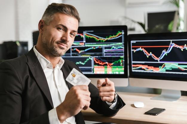 Porträt des europäischen geschäftsmannes der 30er jahre, der anzug hält, der kreditkarte hält, während er im büro sitzt und mit digitaler grafik am computer arbeitet