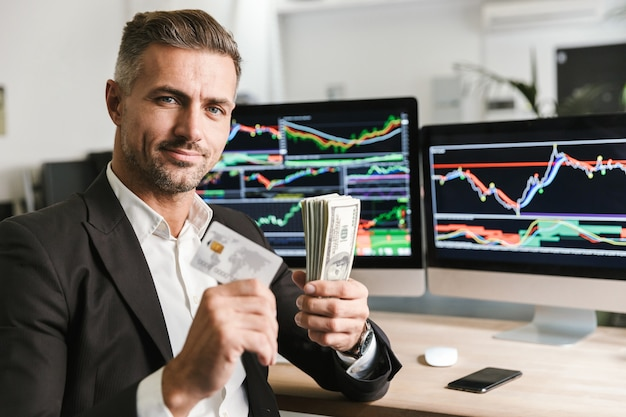 Porträt des europäischen geschäftsmannes der 30er jahre, der anzug hält, der kreditkarte und packung geld hält, während mit der digitalen grafik am computer arbeitet
