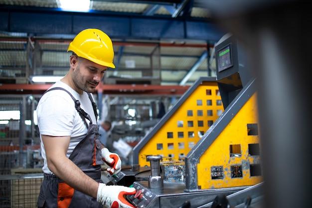 Porträt des fabrikarbeiters, der an der industriemaschine in der produktionsanlage arbeitet