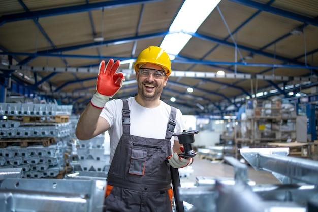 Porträt des fabrikarbeiters in der schutzausrüstung, die daumen hoch in der produktionshalle hält