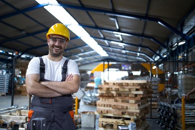 Porträt des fabrikarbeiters mit verschränkten armen, der durch industriemaschine steht