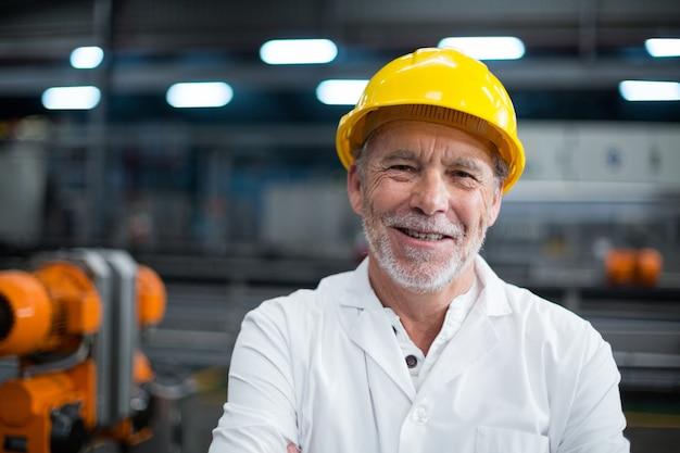 Porträt des fabrikingenieurs, der in der flaschenfabrik steht