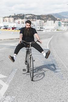 Porträt des fahrrades des jungen mannes reitauf straße mit den beinen herausgeschmissen