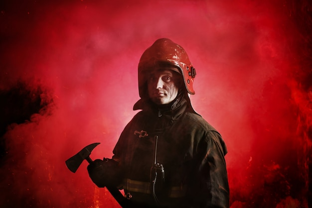 Porträt des feuerwehrmanns in uniform auf dunkelrot