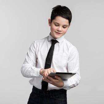 Porträt des firmenjungen, der tablette hält