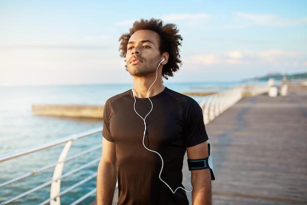 Porträt des fit dunkelhäutigen muskulösen mannläufers mit buschiger frisur, die konzentriert in der schwarzen sportkleidung sieht, die weiße kopfhörer trägt.