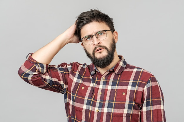 Porträt des fokussierten intelligenten männlichen modells mit mit durchdachtem entschlossenem ausdruck