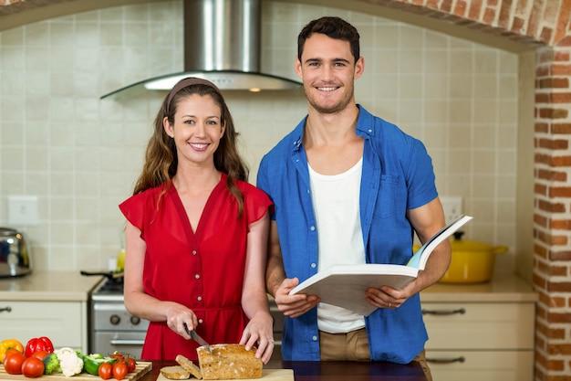 Porträt des frauenausschnittbrotlaibs während mann, der zu hause das rezeptbuch in der küche überprüft