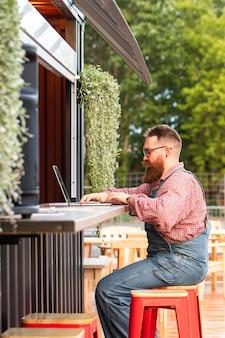 Porträt des freiberuflers des brutalen bärtigen hipster-mannes, der blaue overalls und kariertes hemd trägt, das auf laptop arbeitet