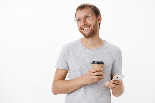 Porträt des freudigen erfreuten kaukasischen erwachsenen kerls mit der borste und im blonden haar in den gläsern, die pappbecher des getränks und des smartphone halten, das mit verträumtem optimistischem lächeln links schaut
