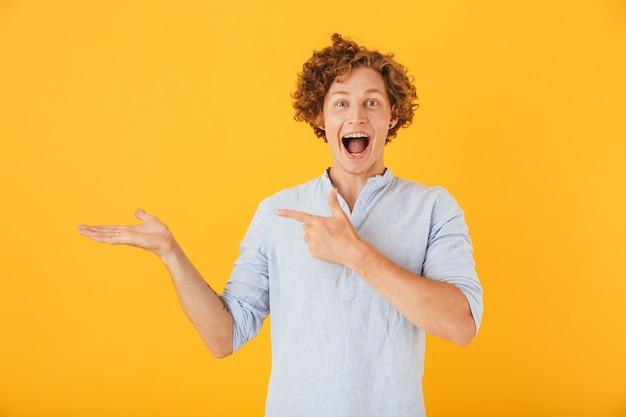 Porträt des freudigen jungen mannes, der lächelt und copyspace an der handfläche hält, lokalisiert über gelbem hintergrund