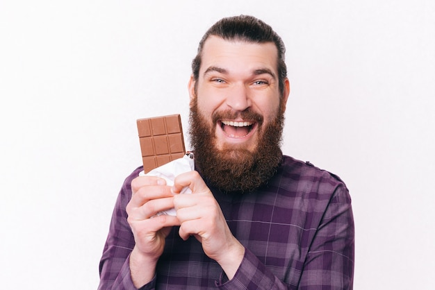 Porträt des freudigen jungen mannes mit bart, der block der schokolade hält