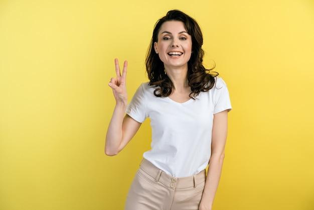 Porträt des freudigen lächelnden mädchens im weißen t-shirt, das v zeichen mit den fingern zeigt und kamera betrachtet, die geste des friedens oder des sieges zeigt