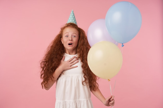 Porträt des freudigen loghaarigen rothaarigen kleinen mädchens, das luftballons in der hand hält, während es über rosa hintergrund steht und von gästen amüsiert wird, lächelt fröhlich. kinder- und feierkonzept