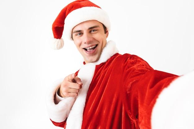 Porträt des freudigen mannes 30s im weihnachtsmannkostüm und im roten hut, die lachen, während selfie-foto machen