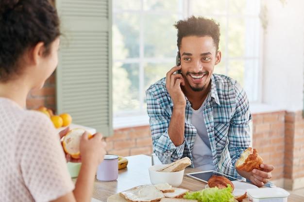 Porträt des freudigen mannes, der froh ist, alten besten freund über handy zu hören,