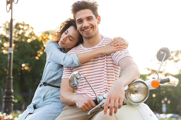 Porträt des freudigen paares, lächelnd und zusammen umarmend, während auf motorrad im stadtpark sitzen