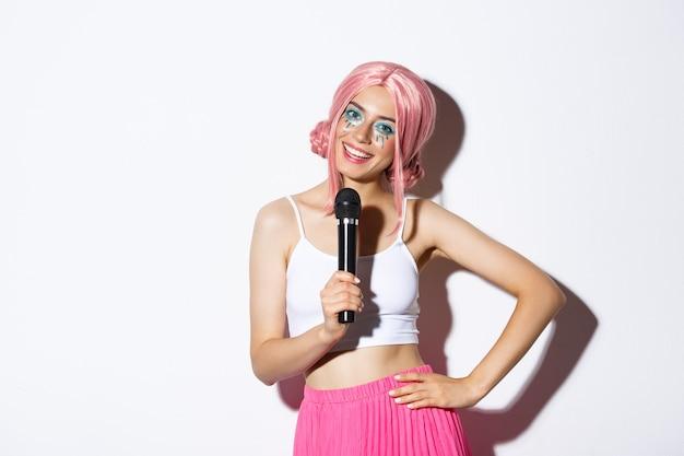 Porträt des freudigen partygirls in der rosa perücke, helles halloween-make-up, singend im mikrofon, stehend.