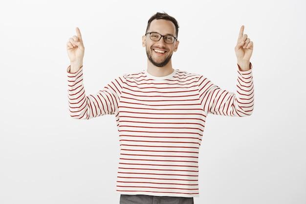 Porträt des freundlichen entspannten europäischen bärtigen mannes in der schwarzen brille, die zeigefinger hebt und nach oben zeigt