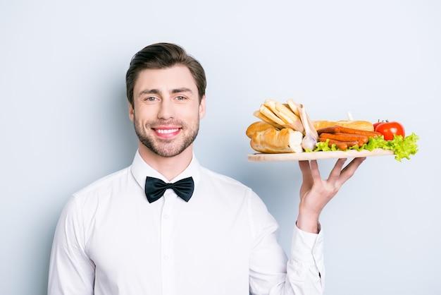 Porträt des freundlichen garcon gekleidet in der formellen kleidung, die essen auf einem teller hält