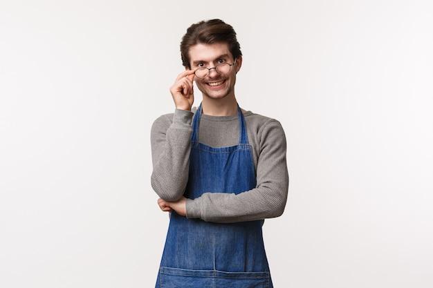 Porträt des freundlichen lächelnden kerls, der im café arbeitet, brillen auf augen repariert und kamera mit enthusiastischem positivem ausdruck schaut, lädt gäste ein, seinen chemex, den besten cappuccino der stadt, zu probieren