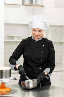 Porträt des freundlichen lächelnden weiblichen professionellen konditors, der einen cupcake mit sahne unter verwendung eines spritzbeutels übersteigt